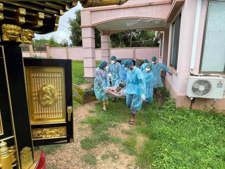 Health workers wearing protective suits carry the body of suspected CVOVID-19 victim in Naypyidaw. Citizen journalist