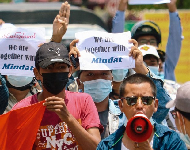 Protesters hold signs, in support of the town of Mindat in Chin state where a civilian defense force has clashed with the military, during a demonstration against the military coup in Mandalay, May 17, 2021.