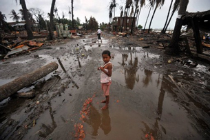 A child stands amongst buildings destroyed in sectarian violence in Sittwe, June 16, 2012.