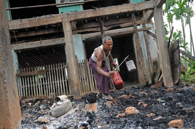 A man salvages items from the burnt area of a mosque following communal clashes in Thabyuchine village in Rakhine state, Oct. 2, 2013. Credit: AFP