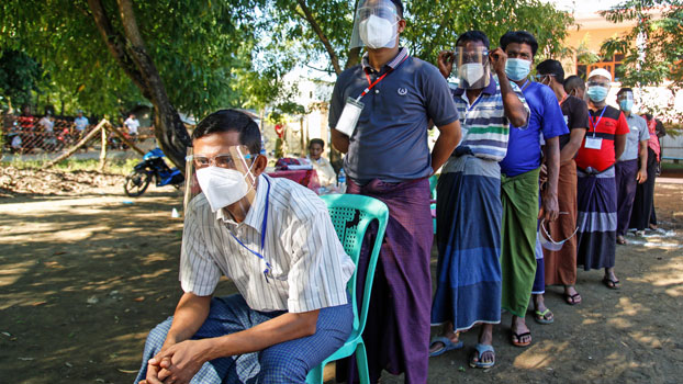 Myanmar voters wearing face shields and face masks to prevent the spread of the coronavirus line up at a polling station in Rakhine state, Nov. 8, 2020.