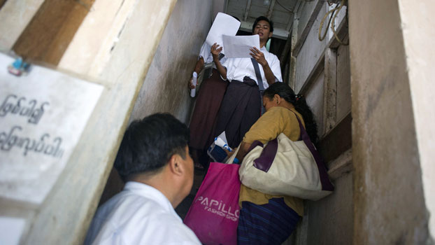 Members of the National League for Democracy check voter lists during a door-to-door visit as part of a voter education campaign in Yangon, June 29, 2015.