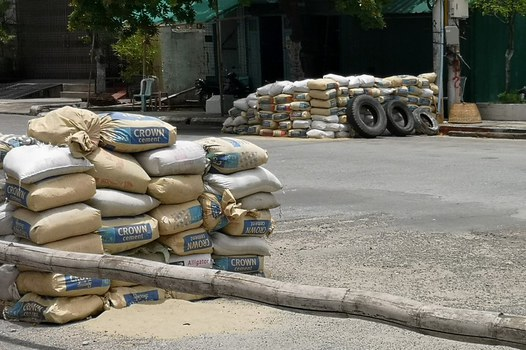 Sand bags stacked by the military and used as a checkpoint are seen along a road in Mandalay on June 23, 2021, following fighting in the streets of Myanmar's second-largest city. AFP