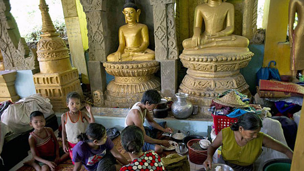 Flood-affected Myanmar villagers eat a meal while taking shelter inside a pagoda in Mrauk-U township, western Myanmar's Rakhine state, Aug. 5, 2015.