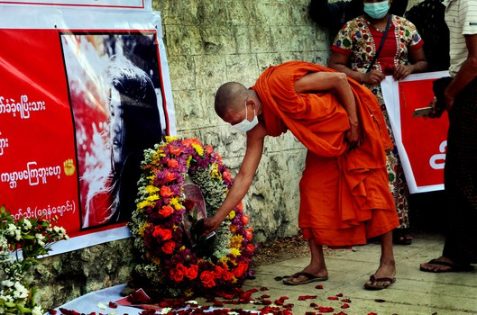 A monk lays flower to commemorate Mya Thwe Thwe Khine, the first protester to die in protests against the Myanmar military coup, in Yenanchaung, Magway Region, Feb. 22, 2021. Credit: Zabyu Min