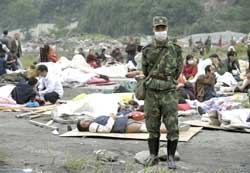 A Chinese soldier stands guard next to injured survivors in Yingxiu of Wenchuan county, after a quake with a magnitude of 7.8 rocked China on May 12, in the southwestern province of Sichuan, on May 15, 2008.  AFP PHOTO / LIU Jin