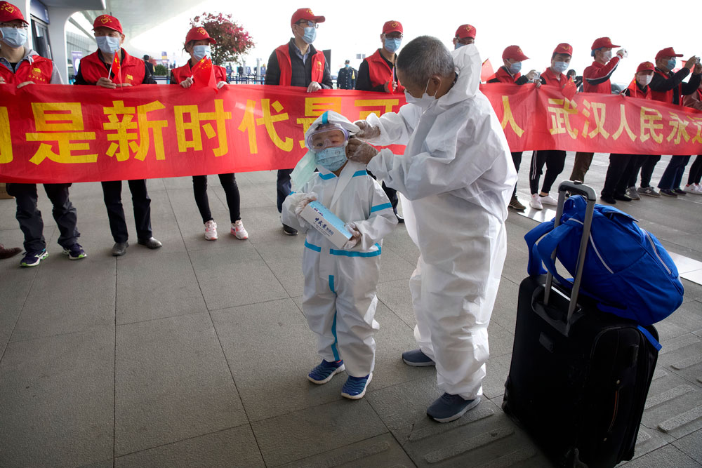 Travelers wearing face masks and suits to protect against the spread of new coronavirus walk past people holding a celebratory banner at Wuhan Tianhe International Airport in Wuhan in central China's Hubei Province, Wednesday, April 8, 2020. (AP Photo/Ng Han Guan)