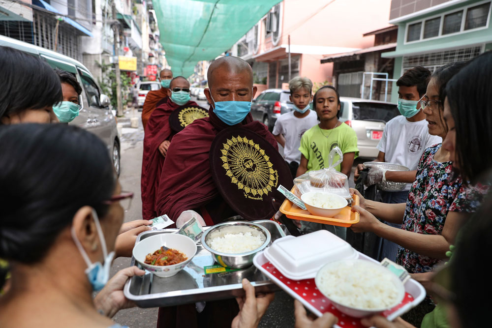 A Buddhist monk wearing face mask and gloves receives alms and cash from devotees in Yangon, Myanmar, Wednesday, April 8, 2020. (AP Photo/Thein Zaw)