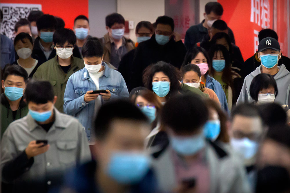 Commuters wear face masks to protect against the spread of new coronavirus as they walk through a subway station in Beijing, Thursday, April 9, 2020.(AP Photo/Mark Schiefelbein)