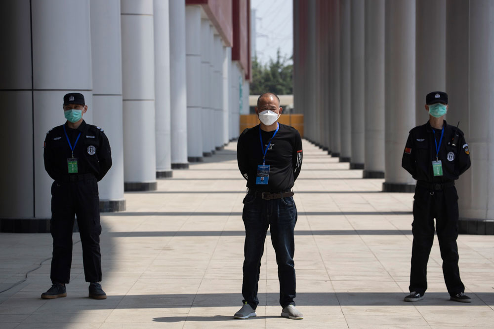 Security guards stand on duty at one of the temporary coronavirus hospitals during a visit by journalists in Wuhan, central China's Hubei province, Thursday, April 9, 2020. (AP Photo/Ng Han Guan)