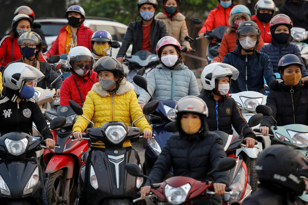Labourers wearing protective masks gather while they wait for a ferry on the way home after work, despite a government rule on social distancing during the coronavirus disease (COVID-19) outbreak in Hai Duong province, Vietnam April 7, 2020. REUTERS/Kham
