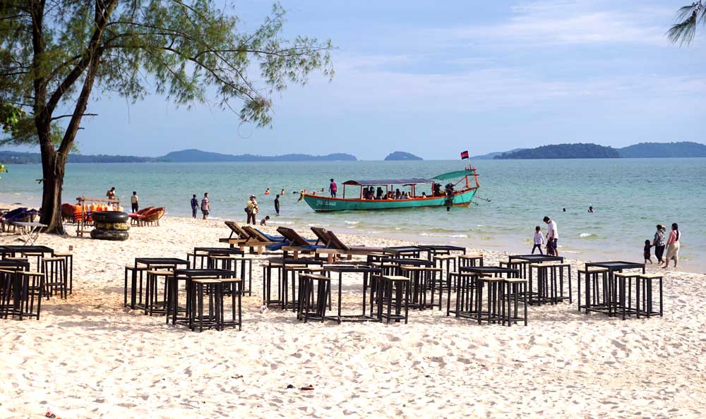 Empty beachside restaurants. Small groups of tourists board a boat for an island day-trip. Chinese expansion in Sihanoukville has led to a decline in other tourists, so local vendors and businesses are struggling. Photo: RFA