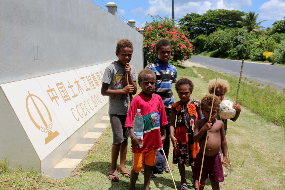 A group of children with fishing spears walk to the beach and past a large commercial Chinese bank. Photo: RFA