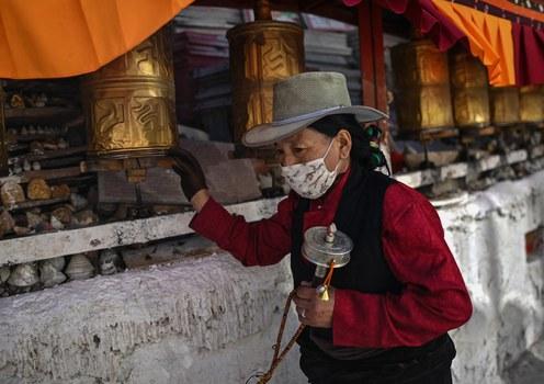 A Tibetan pilgrim prays next to a Buddhist shrine in Tibet's regional capital Lhasa, June 3, 2021.