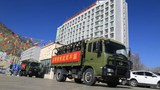 Trucks carrying Chinese security troops move through the streets of Tibet's Lhoka city in a March 2021 photo.