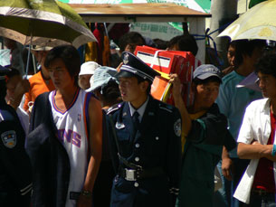 Chinese policeman moves through a crowd of Tibetans. Photo: True Vision