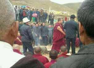 Monks and onlookers stand around the burned body of Tamdin Dorjee at the Tsoe monastery, Kanlho prefecture, Oct. 13, 2012.