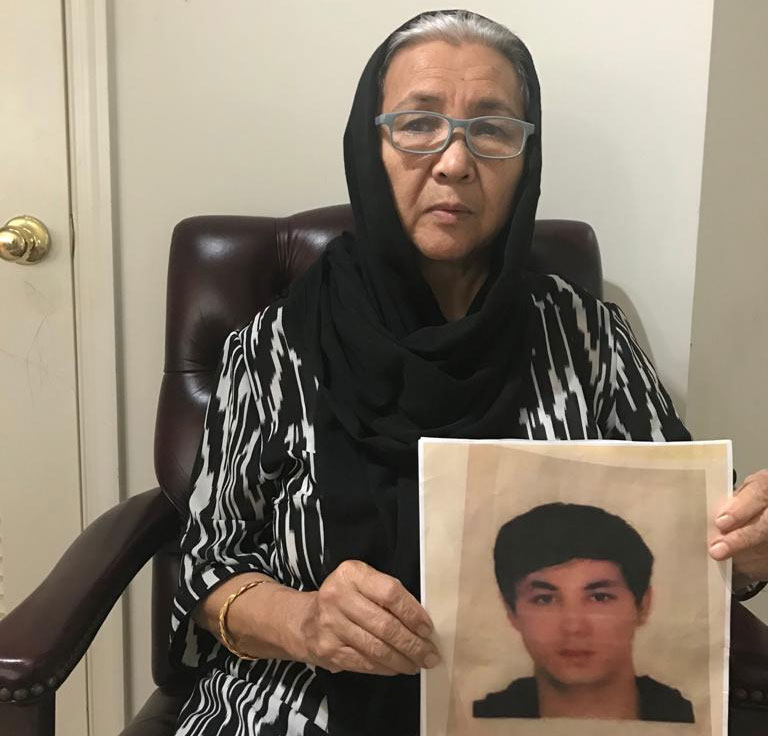 Hurshida Hasan holds a portrait of her nephew Abdughopur Abdureshid at her home in Virginia, in an undated photo.