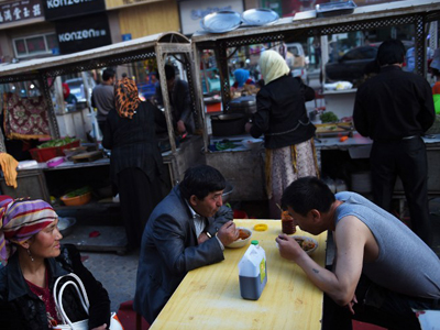 Uyghurs eat at a food stall in a night market in Hotan, April 15, 2015. Credit: AFP