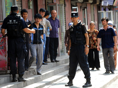 Chinese riot police keep watch on Uyghur residents near a mosque in Urumqi following ethnic violence between Uyghurs and Han Chinese, July 10, 2009. Credit: AFP