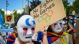 Uyghur and Tibetan activists hold placards and wear masks during a protest against the Beijing 2022 Winter Olympics in front of the Olympics Museum in Lausanne, Switzerland, June 23, 2021.