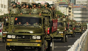 Chinese paramilitary police trucks drive through downtown Urumqi, July 9, 2009. AFP
