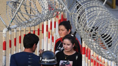 A Uyghur woman (C) walks through a security checkpoint to enter a bazaar in Hotan, in China's Xinjiang Uyghur Autonomous Region (XUAR), May 31, 2019.