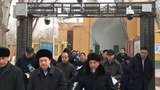 Imams and government officials pass under security cameras as they leave the Id Kah Mosque during a government-organized trip in Kashgar, XUAR, Jan. 4, 2019.