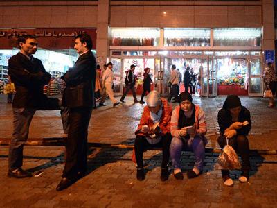 Young Uyghurs rest near the Grand Bazaar in Urumqi, Sept. 17, 2014. Credit: AFP