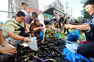 "A New China News agency (Xinhua) picture showing ""Urumqi residents buying vegetables at a market,"" as proof that normalcy has returned to the regional capital on July 10."