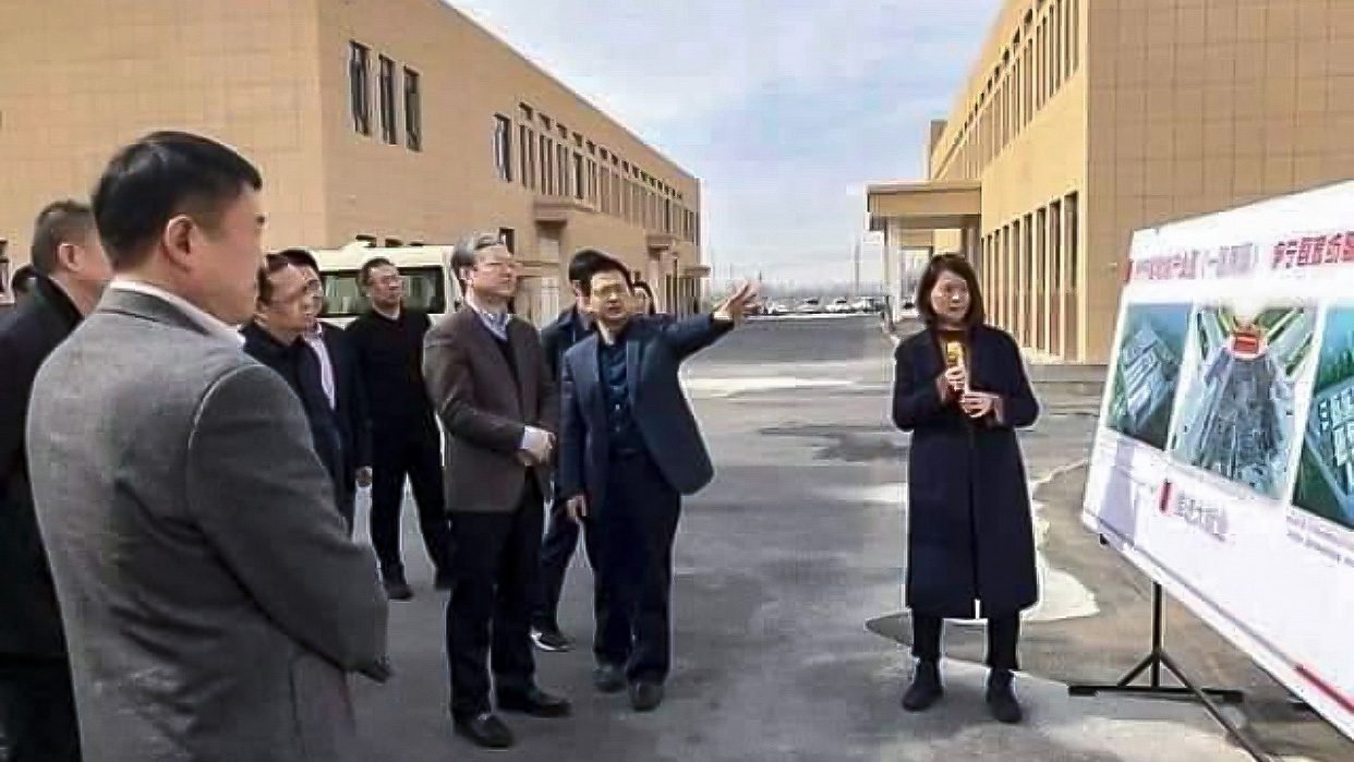 Visiting officials are briefed outside of the Zhuowan factory, in an undated photo.