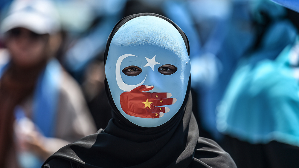 A demonstrator wearing a mask painted with the colors of the flag of East Turkestan and a hand bearing the colors of the Chinese flag attends a protest against Beijing's treatment of Uyghurs in front of the Chinese consulate in Istanbul, July 5, 2018. Credit: AFP