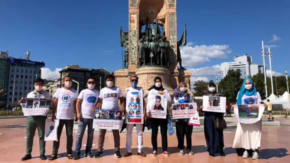 Uyghurs wearing T-shirts with images of missing relatives pose for a photo in front of the Republic Monument on Taksim Square in Istanbul, Aug. 17, 2020.