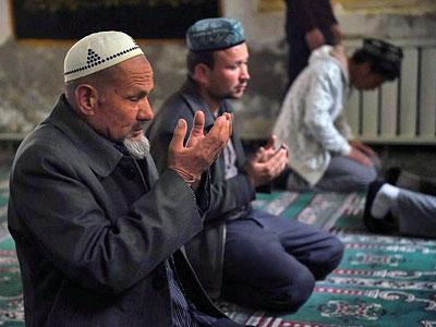 Uyghur men pray inside a mosque in Hotan in China's northwestern Xinjiang region, April 16, 2015.