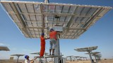 Workers check a solar panel at a field in Kumul (in Chinese, Hami) in orthwest China's Xinjiang Uyghur Autonomous Region, Aug. 6, 2012.