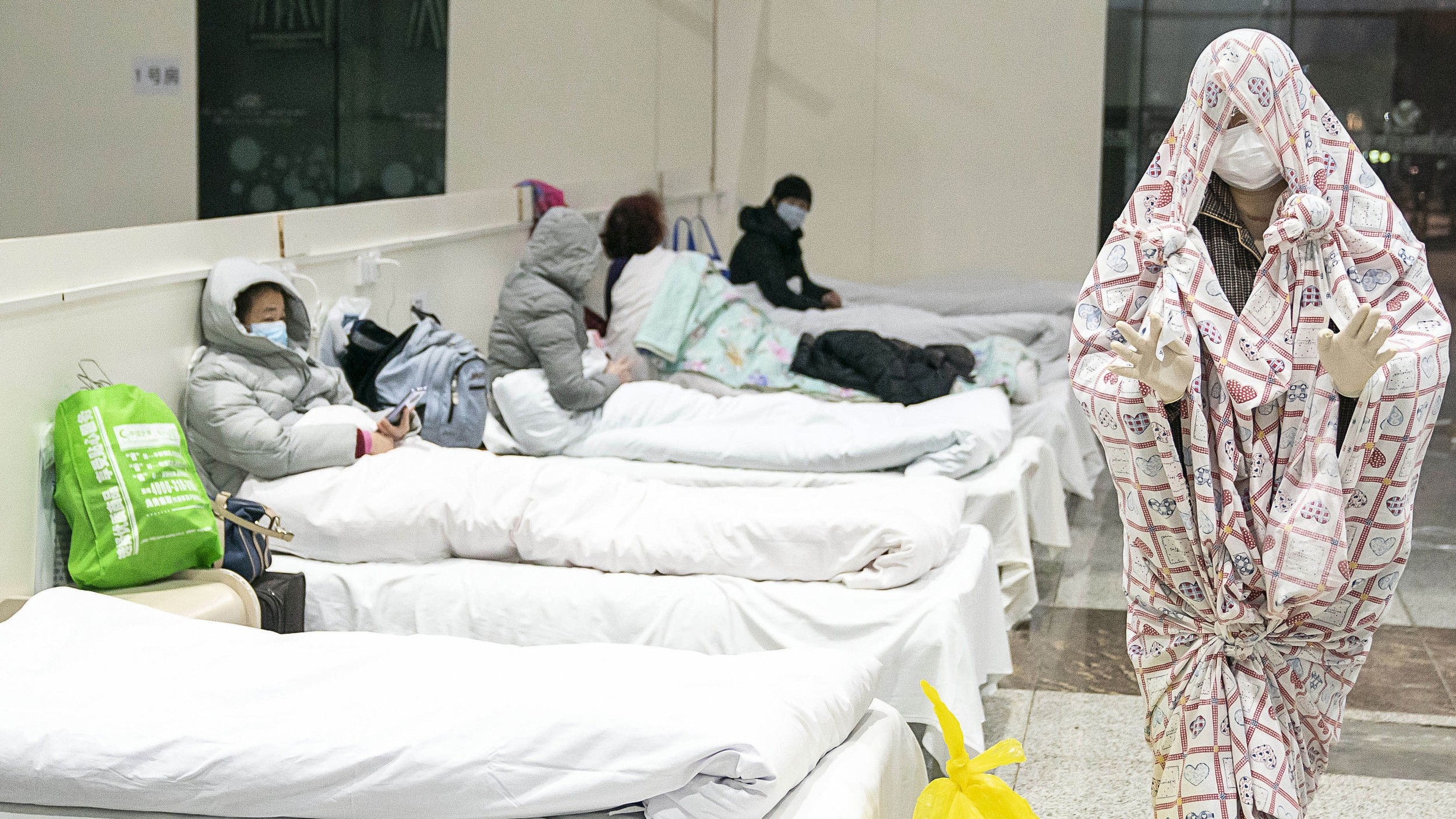 A patient (R) covered with a bed sheet gestures at an exhibition center converted into a hospital in Wuhan, in China's central Hubei province, Feb. 5, 2020. Photo: AFP