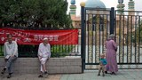 Uyghur residents gather outside a mosque with Chinese slogans on a banner on its fence in the city of Aksu (in Chinese, Akesu) in northwestern China's Xinjiang Uyghur Autonomous Region, July 17, 2014.