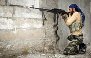 A rebel fighter fires his machine gun at Syrian government troops in the town of Harem, Oct. 31, 2012.