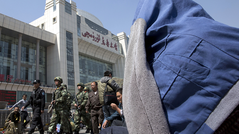 Chinese paramilitary police march past the Urumqi South Railway Station in Urumqi, in a file photo. Credit: AP Photo