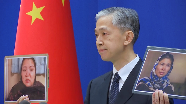 Chinese Foreign Ministry spokesman Wang Wenbin holds pictures of former internment camp detainees while speaking during a news conference in Beijing, Feb. 23, 2021, in this still image taken from video. Reuters
