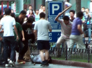 An AFP TV grab shows a mob of Han Chinese attacking a lone Uyghur man along a street in Urumqi, July 8, 2009. AFP