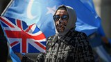 A Uyghur woman holds the flag adopted by the East Turkestan independence movement and the Union Jack during a demonstration calling on the UK parliament to vote to recognize alleged persecution of China's Muslim minority Uyghur people as genocide and crimes against humanity, in London, April 22, 2021.