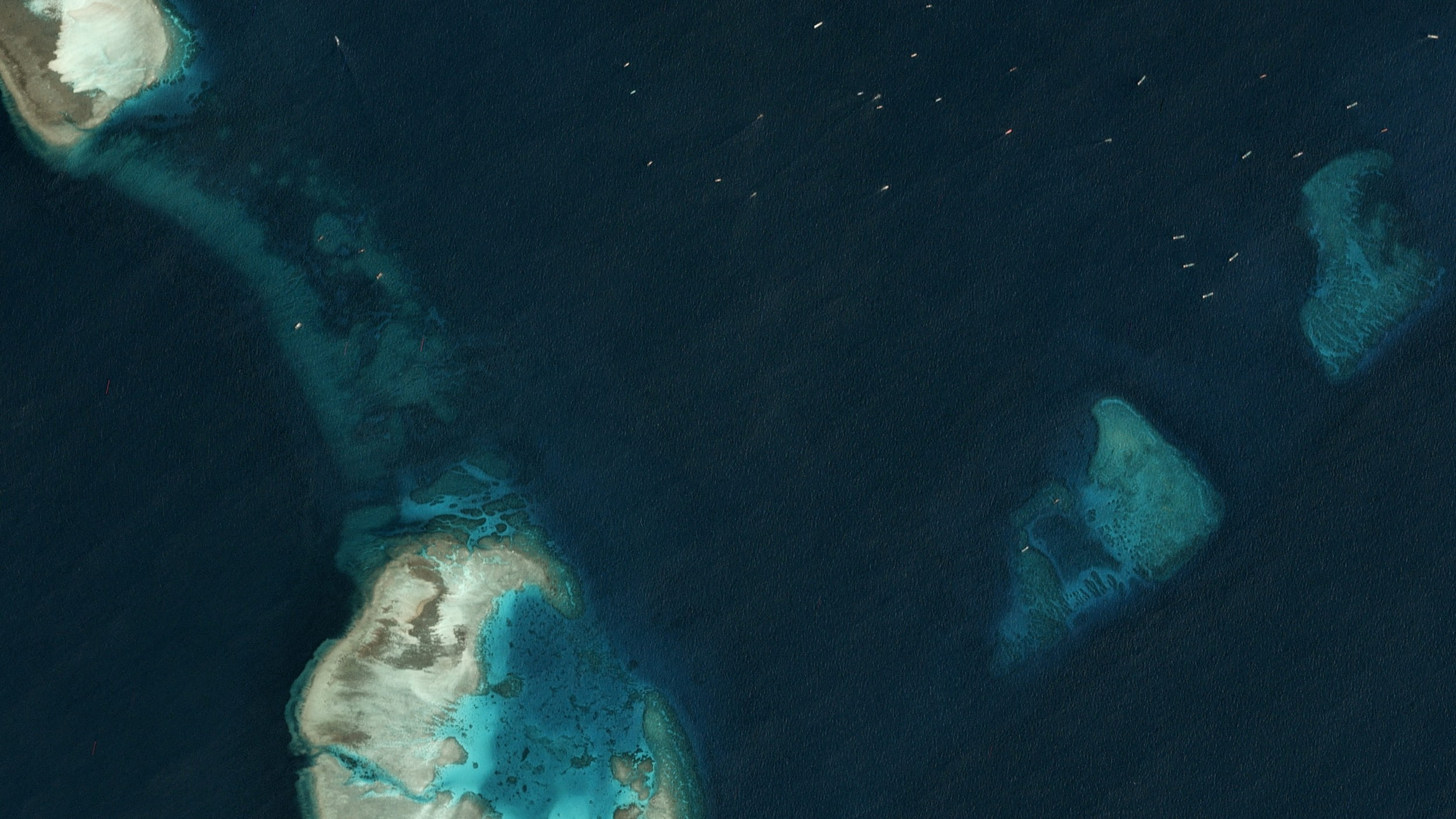 Satellite image taken just north of the Chinese-occupied base at South Johnson Reef, in which multiple, unidentified vessels can be seen in the top right hand corner, March 22, 2020.