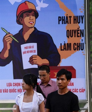 People walk past a propaganda poster featuring the elections in downtown Hanoi on May 19, 2011.