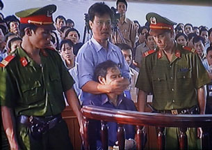 A security officer covers the mouth of Father Thadeus Nguyen Van Ly after he shouts in protest during his trial at a court in Hue, March 30, 2007. Credit: AFP