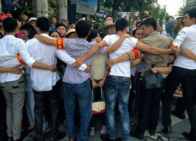 Vietnamese plainclothes policemen form a human chain to prevent protestors from approaching the People's Court in Hanoi, Oct. 2, 2013. Credit: AFP