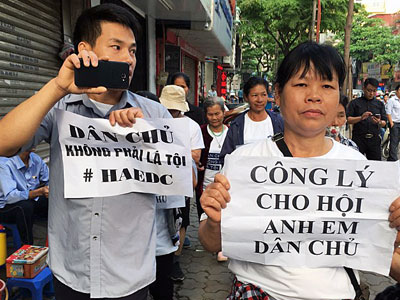 Vietnamese protesters display placards as they march towards a courthouse during the trial of a prominent rights lawyer and five other activists in Hanoi, April 5, 2018.