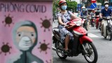 Motorists wearing protective face masks ride past an electricity box painted decorated with a coronavirus-themed painting along a street in Vietnam's capital Hanoi, July 8, 2021.