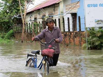 A man walks his bike along a flooded street in Cambodia's Siem Reap, Oct. 1, 2013. Photo credit: RFA.