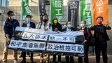 Hong Kong pro-democracy activists shout slogans in support of veteran activists outside the West Kowloon Magistrates Court in Hong Kong as they go on trial for organizing one of the biggest democracy protests to sweep the city in 2019, Feb. 16, 2021,